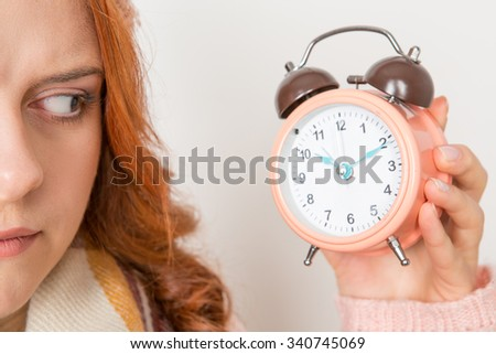 Time is out. Closeup of serious red haired female looking at the clock in her hand angrily  - stock photo