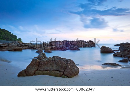Time-lapse of beach at dusk with rocks - stock photo