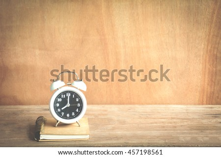 Time management concept:Alarm clock set at 8:00 on a notebook. - stock photo
