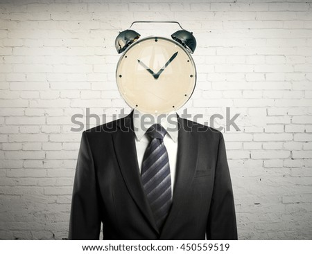 Time management concept with alarm clock headed businessman on white brick background