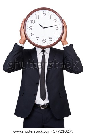 Time management. Man in formalwear holding clock over his face while standing isolated on white background