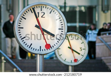 Time pieces at London docklands, the new financial district of London, with office workers visible in the background. - stock photo