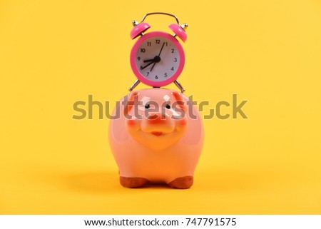 Time save Concept. Pink piggy bank with stopwatch on top on yellow background. Time is money