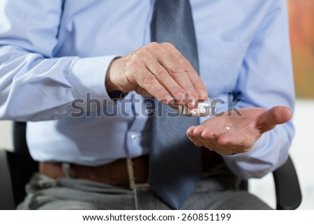 Time to a medication for elderly man at home - stock photo