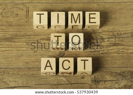 time to act ext on wooden cubes on a wooden background