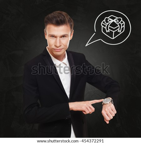Time to buy present. Businessman point at his hand watch showing clock. Man in suit at black background, thinking cloud with present box. Holidays, celebration and congratulation concept - stock photo