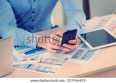 Time to call the customer. Confident businessman holding a cell phone in hand. Close-up view of the hands of a businessman in the office of the table in the formal wear. - stock photo