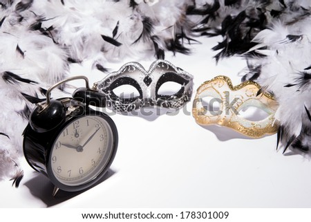 Time to celebrate. Alarm clock with Mardi Gras mask and feather boa - stock photo