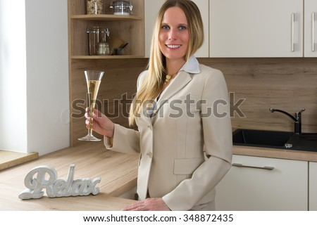Time to celebrate: business woman with a glass of champagne relaxing in a modern kitchen
