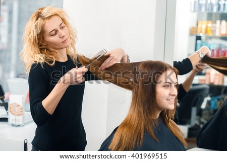 Time to change. Beautiful happy female smiling cheerfully as she is getting a new haircut at the local salon