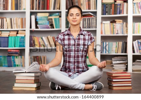 Time to chill. Beautiful young woman keeping her eyes closed and meditating while sitting at the library - stock photo