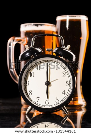 time to drink beer. glasses of fresh lager beer with clock on black with reflection - stock photo