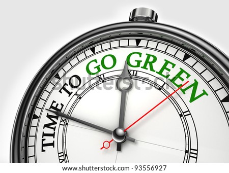 time to go green concept clock closeup on white background with red and black words - stock photo