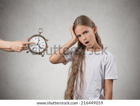 Time to go to bed. Portrait of mom showing kid clock that it is late. She doesn't like that, isolated grey wall background. Face expressions, emotions. Difficult parenting concept - stock photo