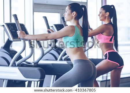 Time to hit the gym. Side view of young beautiful women with perfect bodies in sportswear looking away while working out on stepper at gym - stock photo