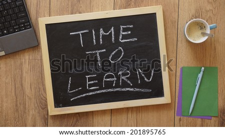 Time to learn written on a chalkboard at the office - stock photo