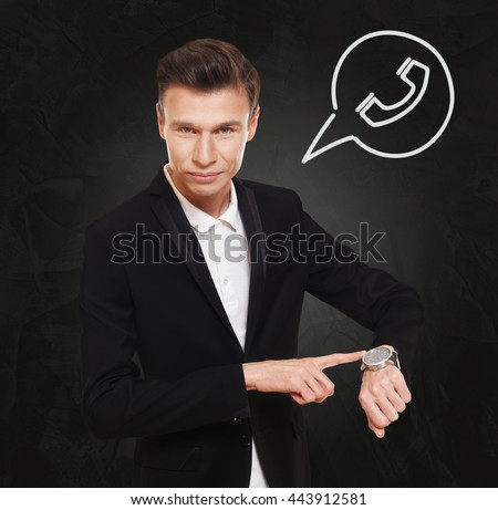 Time to make a call. Businessman in suit points at his watch at black background, thinking cloud with old phone receiver symbol. Communication concept - stock photo
