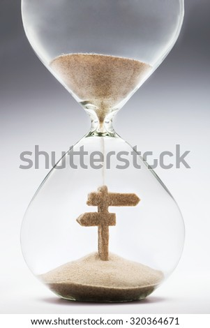 Time to make plans for summer vacation. Hourglass falling sand taking the shape of directional signpost - stock photo