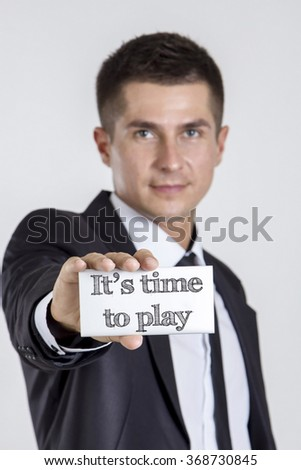 time to play - Young businessman holding a white card with text - vertical image