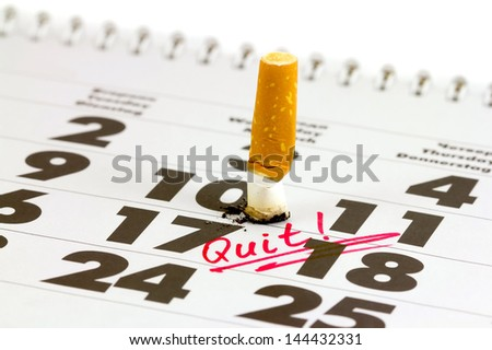Time to quit smoking. Cigarette butts on the calendar. Concept of choosing a day to quit smoking - stock photo