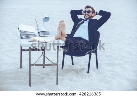 Time to relax. Handsome young man in formalwear and sunglasses holding hands behind head and holding his feet on the table standing on sand - stock photo