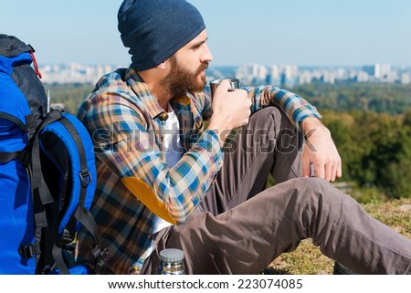 Time to relax. Handsome young man sitting near backpack and looking away while drinking  - stock photo