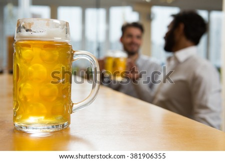 Time to relax. Selective focus on a glass of beer businessman enjoying drinks on the background  - stock photo