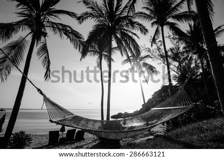 Time to relax with silhouette of hammock and coconut tree at the beach on sunset time in Samui Island Thailand with black and white color - stock photo