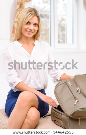 Time to settle. Young nice-looking female tourist opens her suitcase and starts unpacking it.  - stock photo