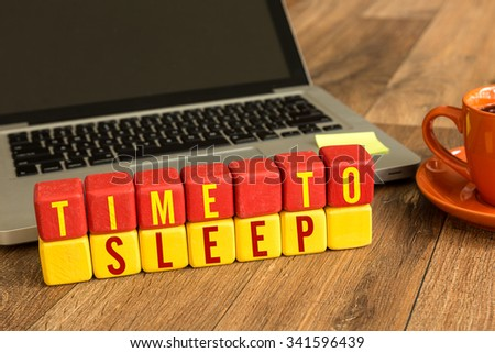 Time to Sleep written on a wooden cube in a office desk - stock photo