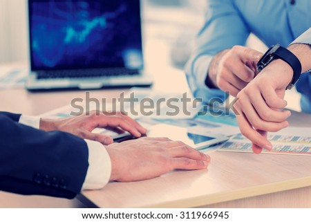 Time to start to work. Close-up view of hands pointing at his watch while two successful businessman sitting at the table against each in the business office in formal wear and work at a laptop. - stock photo