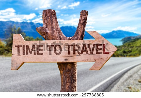 Time to Travel wooden sign with road background - stock photo