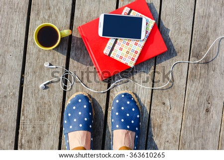 Time to work/study. Lifestyle, summer vacation, education and people concept. Young hipster girl's feet with coffee cup, smartphone, headphones, stacked books on wooden background - stock photo