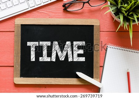 Time word Handwritten on blackboard. Time word Handwritten with chalk on blackboard, keyboard,notebook,glasses and green plant on wooden background - stock photo