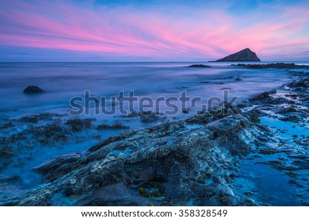 Timelapse sunset and blur water at atlantic rocky beach in Wembury Devon, UK. - stock photo