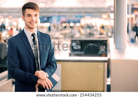 Timely check-in. Handsome young businessman in suit holding his passport with ticket and luggage while standing against airline check in counter in the airport - stock photo