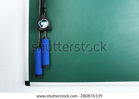 Timer and skipping rope on blackboard background - stock photo
