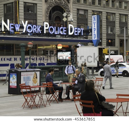 Times Square, New York, USA June 8, 2015 People hurry to work while other workers have coffee in the morning while sitting in pedestrian space in Times Square near NY Police Department HQ - stock photo