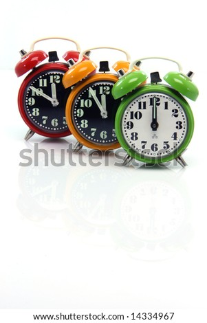 timing red yellow and green alarm clock until twelve o'clock closeup with nice small reflection vertical - stock photo