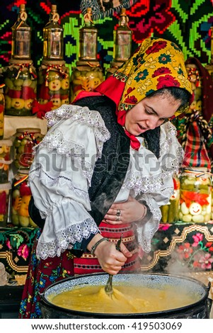 TIMISOARA, ROMANIA - DECEMBER 20, 2014: Young woman dressed in traditional costume from Maramures, Romania, mixed polenta in a large pot. - stock photo