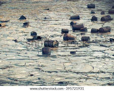 Tin barrels are floating on a oily water surface. - stock photo