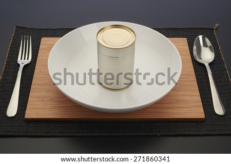 Tin can put on plate with spoon and knife  - stock photo