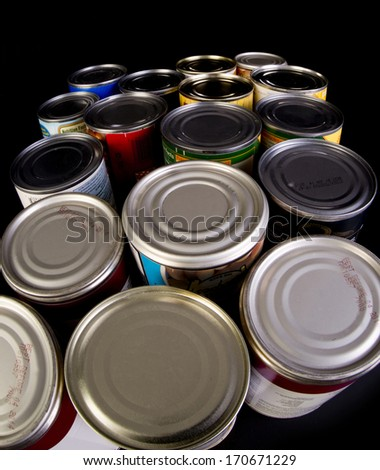 Tin cans on black background. - stock photo