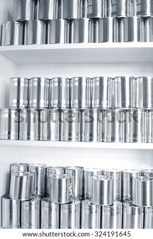 Tin cans stacked on shelves - stock photo