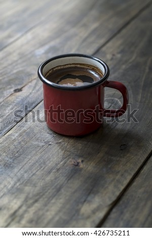 Tin mug with coffee on wooden background
