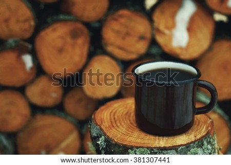 tin mug with coffee. Tree stumps as background