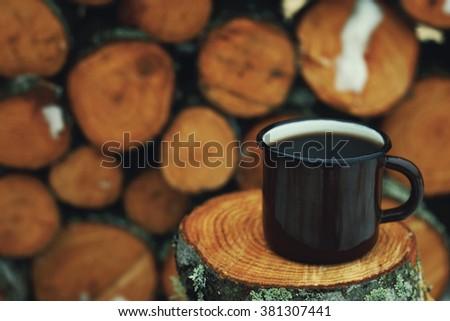 tin mug with coffee. Tree stumps as background - stock photo