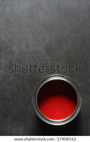 tin of vibrant red paint on slate background