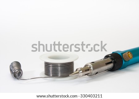 Tin solder and a soldering iron on gas on a white background. - stock photo
