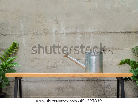 tin watering can on wooden bench with concrete wall in backyard